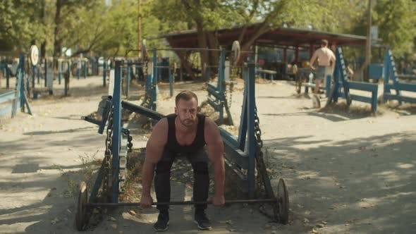 Bodybuilder Doing Weightlifting Workout Outdoors