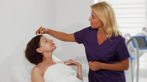 Professional Cosmetologist Examining Face of Her Female Client