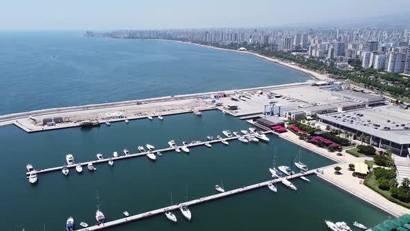 Aerial view of yachts and boats moored at marina and panorama of seaside city
