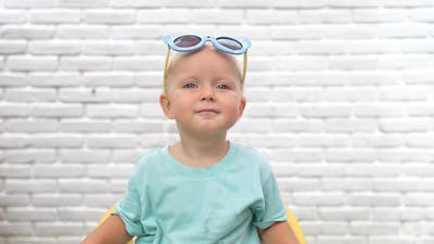 Cheerful Blonde with Blue Sunglasses on Head Looking to the Camera