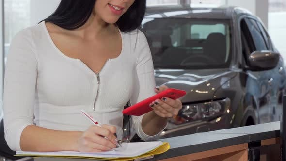 Thumbnail for Female Customer Using Smart Phone While Signing Documents for New Automobile