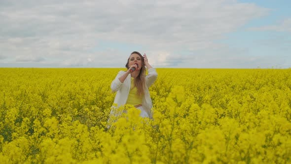 Thumbnail for A Beautiful Woman Dances Looks at the Camera and Sings Standing in a Yellow Field. Female Singer