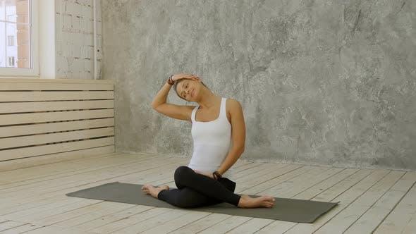 Thumbnail for Porträt von Reife Frau Stretching Ihr Hals und Blick weg auf Yoga-Klasse