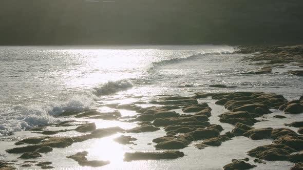 Lanzarote coastline with ocean waves washing volcanic stones, scene in sunlight