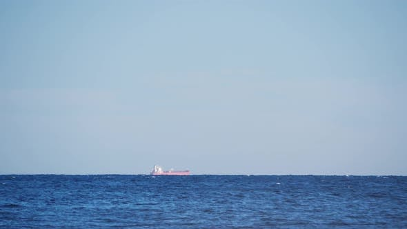 Timelapse of Container Ship Sailing Along the Horizon. Huge Container Ship Floating in the Sea