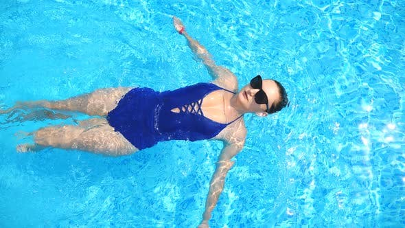 Woman Swimming on Back Through Pool with Crystal Clear Water. Elegant Girl in Sunglasses Relaxing on