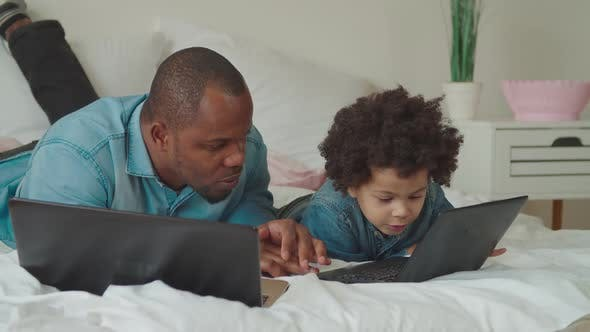 Thumbnail for Caring Black Dad Teaching Son Using Laptop at Home