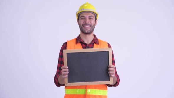 Thumbnail for Happy Bearded Persian Man Construction Worker Holding Blackboard