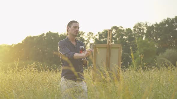 Thumbnail for Concentrated Caucasian Man Painting Landscape at Sunset. Portrait of Inspired Male Painter with