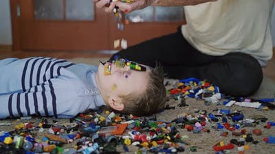 Excited boy and his grandfather playing with lots of colorful plastic toys. Educational toys.