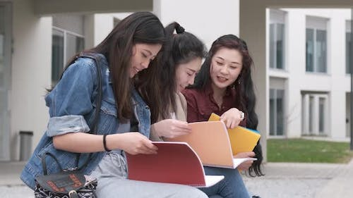 three asian girl students talking at break time sitting on campus