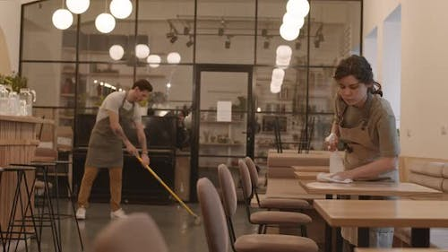 Male and Female Waiters Cleaning Cafe