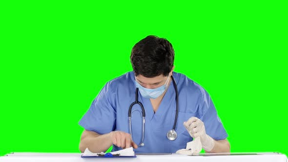 Cover Image for Doctor Removes Medical Gloves and Using Laptop. Green Screen