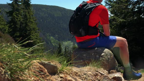 Thumbnail for Young Man Sits on the Stone in the Middle Pathway To the Top of the Mountain and Looks Around
