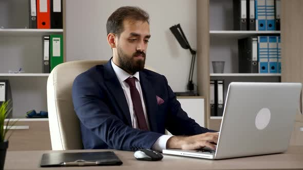 Thumbnail for Attractive Young Businessman in the Office Types on the Computer Then Looks in a Folder with Charts