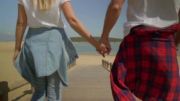 Thumbnail for Cropped Shot of Couple Holding Hands and Walking on Beach