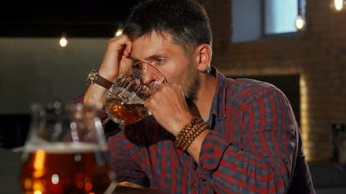 Depressed Man Drinking Alone at the Bar