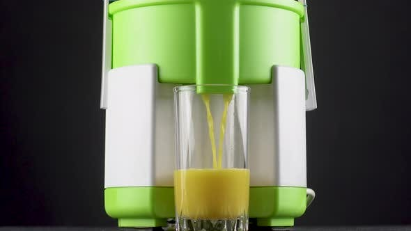 Freshly Squeezed Orange Juice Is Poured Into a Glass Cup From a Juicer