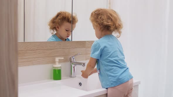 Young Girl Washing Hands with Water