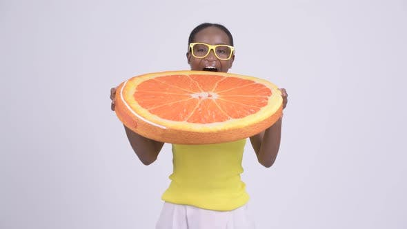 Thumbnail for Young Happy African Woman Biting Orange Pillow As Healthy Concept