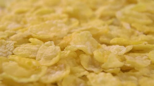 Crispy dry cornflakes fall in a heap in a slow motion
