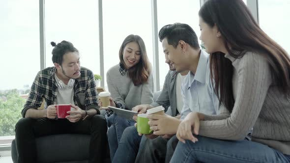 People group team holding coffee cups and discussing ideas meeting with tablet sitting on the couch