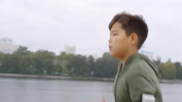Thumbnail for Asian Boy with Smartphone in Armband Running along Urban Riverside