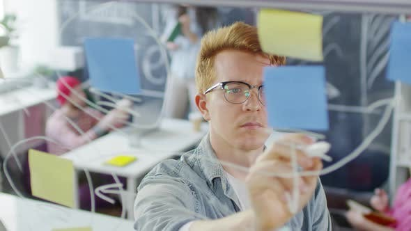 Thumbnail for Red-Haired Caucasian Man Looking at Diagram in Creative Office