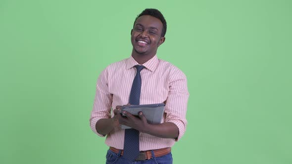 Thumbnail for Happy Young African Businessman Thinking While Using Digital Tablet
