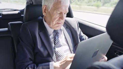 Senior Businessman with Laptop in Car