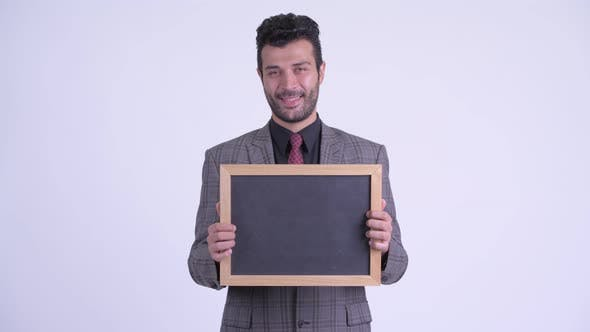 Thumbnail for Happy Bearded Persian Businessman Thinking While Holding Blackboard