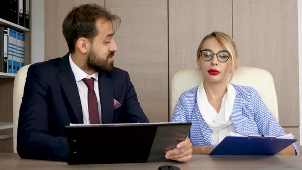 Thumbnail for Two Business Partners Discussing and Analyzing Strategy Business on Clipboards with Charts