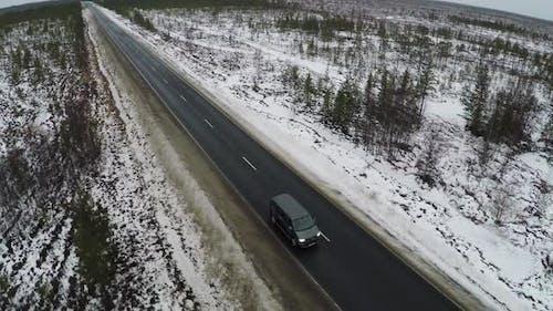 Aerial view of minivan driving winter road