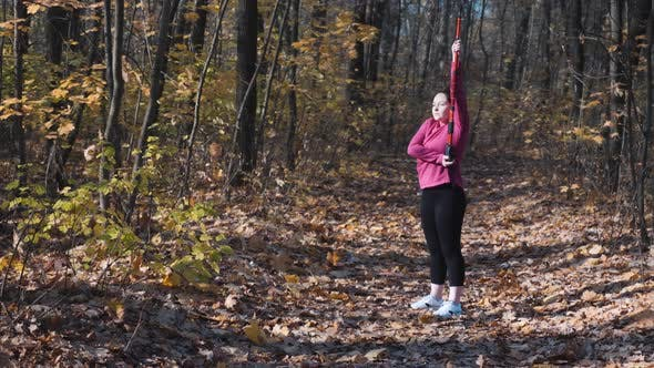 Thumbnail for Woman with nordic walking poles stretching her arms and body before outdoor sports activity