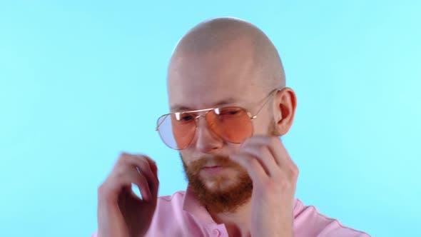 Bearded Man Putting On Sunglasses