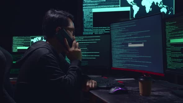 Asian Male Hacker Talking On Phone With Multiple Computer Screens And Success Downloading Data
