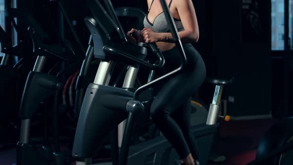 Girl Doing Sports In A Gym. Elliptical trainers. Fitness Center.