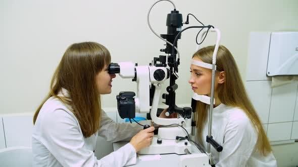Woman checks her eyesight with optical equipment