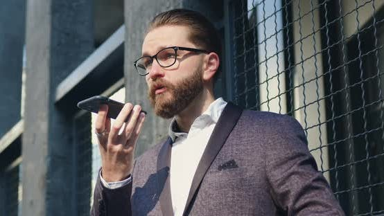 Thumbnail for Businessman in Glasses Agrees on Meeting with His Business Partner on Phone while Standing Outdoors