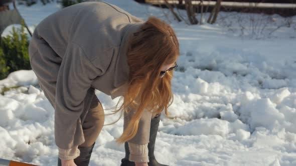 Female Cleans Snow