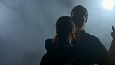 Portrait Romantic Couple Dancing in a Dark Room with Smoke