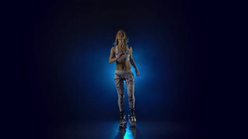 Blonde with a Sporty Physique Dancing Against Blue Spotlight