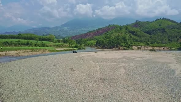 Jeep Drives on Pebble Riverbed Against Green Hills Sky