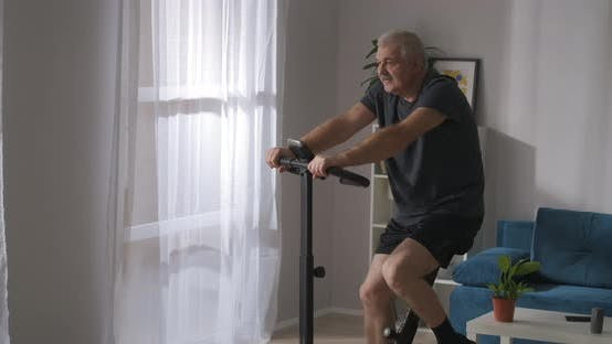 Fitness and Healthy Lifestyle in Middle Age Adult Man Is Training with Exercycle in Living Room