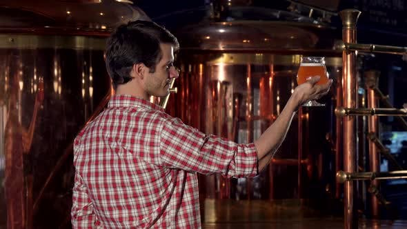 Thumbnail for Rear View Shot of a Happy Brewer Showing Thumbs Up After Examining Beer