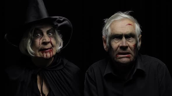 Thumbnail for Elderly Man and Woman in Halloween Costumes. Dripping Blood on Their Faces