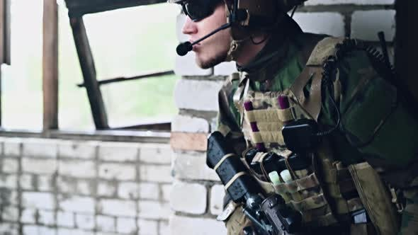 Thumbnail for Military Man with Assault Rifle Standing Inside Building, He Is Ready for Combat