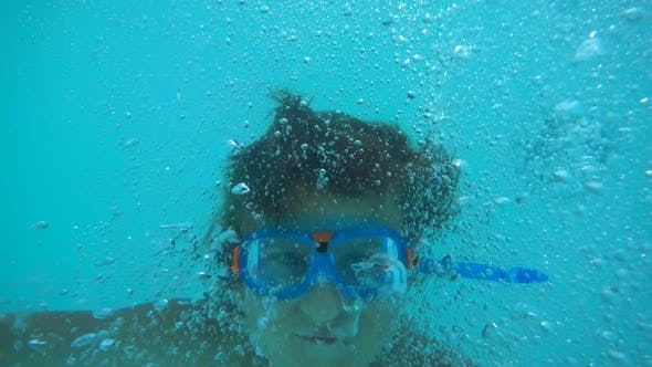 Underwater shot of a boy playing in a pool at a hotel resort.