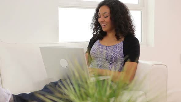 Thumbnail for Woman in living room with laptop computer