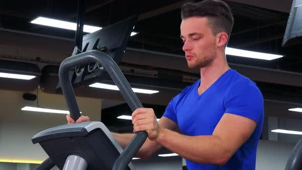 Thumbnail for A Young Fit Man Trains on a Machine in a Gym - Closeup